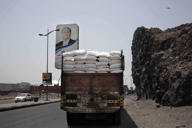 FILE - In this July 23, 2018 file photo, a truck carries aid on a road in Aden, Yemen. The U.N. says that a dozen humanitarian organizations in war-torn southern Yemen have suspended their work after a string of targeted attacks. Meanwhile, the country's rebel-led health ministry announced on Tuesday, Dec. 24, 2019, that severe outbreaks of swine flu and dengue fever have killed close to 200 people since October. (AP Photo/Nariman El-Mofty, File)
