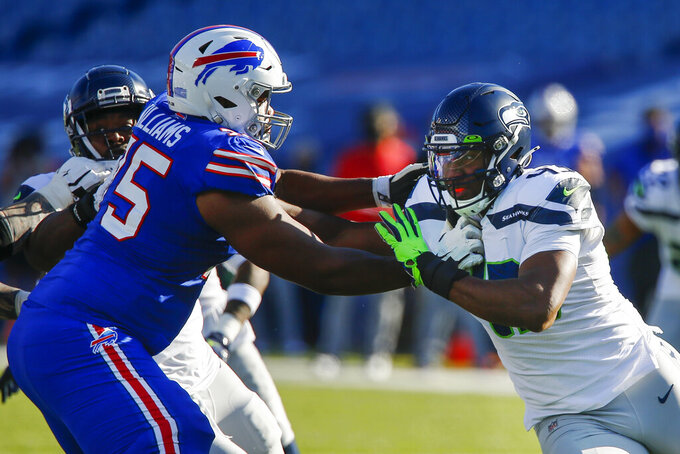 Seattle Seahawks Carlos Dunlap, right, works to get past Buffalo Bills offensive tackle Daryl Williams (75) during the first half of an NFL football game Sunday, Nov. 8, 2020, in Orchard Park, N.Y. (AP Photo/John Munson)