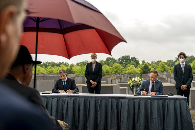 U.S. Secretary of State Antony Blinken, left, and German Minister of Foreign Affairs Heiko Maas, right, sign an agreement during a ceremony for the launch of a U.S.-Germany Dialogue on Holocaust Issues at the Memorial to the Murdered Jews of Europe in Berlin, Thursday, June 24, 2021. Blinken is on a week long trip in Europe traveling to Germany, France and Italy. (AP Photo/Andrew Harnik, Pool)