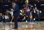 Boston Celtics head coach Brad Stevens looks over his notes during a timeout as the Celtic dancers perform behind him during the third quarter of an NBA basketball game against the Milwaukee Bucks Wednesday, Oct. 30, 2019, in Boston. (AP Photo/Winslow Townson)