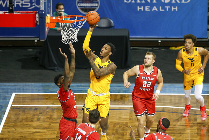 West Virginia forward Gabe Osabuohien (3) shoots the ball over a Western Kentucky defender during the first half of an NCAA college basketball game Friday, Nov. 27, 2020, in SIoux Falls, S.D. (AP Photo/Josh Jurgens)