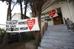 Signs are posted outside of a house that was occupied by homeless women in Oakland, Calif., Tuesday, Jan. 14, 2020. Homeless women ordered by a judge last week to leave a vacant house they occupied illegally in Oakland for two months have been evicted by sheriff's deputies. They removed two women and a male supporter Tuesday from the home before dawn in a case highlighting California's severe housing shortage and growing homeless population. (AP Photo/Jeff Chiu)