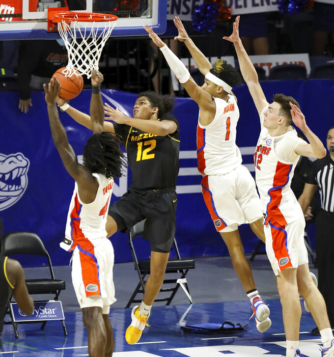Missouri guard Dru Smith (12) goes up and under the basket to score the game winning basket against Florida during an NCAA college basketball game, Wednesday, March 3, 2021 in Gainesville, Fla. (Brad McClenny/The Gainesville Sun via AP)