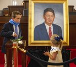 CORRECTS NAMES OF GRANDCHILDREN TO MARC CREW MORAN AND KENNEDY MORAN INSTEAD OF MARC CREW AND KENNEDY CREW - Marc Basnight's grandchildren Marc Crew Moran and sister Kennedy Moran look over a portrait of their grandfather former Senate President Pro Tempore Marc Basnight, after it was unveiled during a ceremony on Tuesday, Sept. 21, 2021, at the General Assembly in Raleigh, N.C. (Robert Willett/The News & Observer via AP)