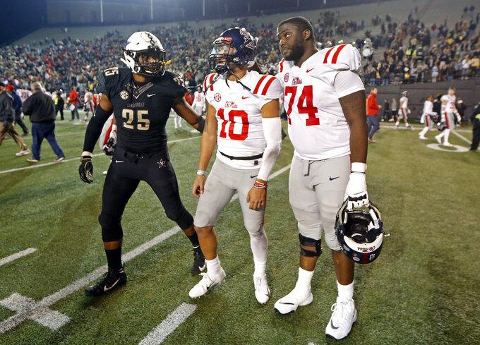 Mississippi quarterback Jordan Ta'amu (10) is consoled by offensive lineman Greg Little (74) and Vanderbilt linebacker Josh Smith (25) after Vanderbilt won 36-29 in overtime in an NCAA college football game Saturday, Nov. 17, 2018, in Nashville, Tenn. (AP Photo/Mark Humphrey)