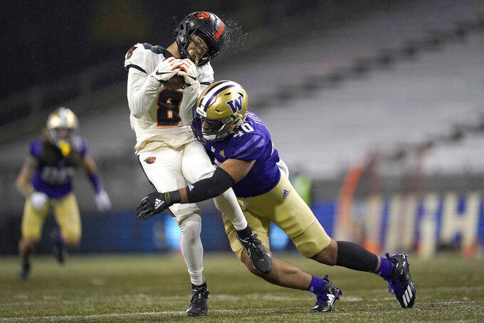 Rain water flies off the helmet of Oregon State wide receiver Trevon Bradford (8) as he is hit by Washington linebacker Alphonzo Tuputala (40) during the second half of an NCAA college football game, Saturday, Nov. 14, 2020, in Seattle. Washington won 27-21. (AP Photo/Ted S. Warren)