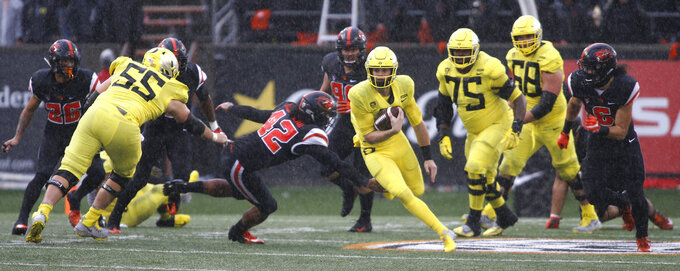 Oregon quarterback Braxton Burmeister, center right, gets past Oregon State linebacker Doug Taumoelau (42) in the second half of an NCAA college football game in Corvallis, Ore., Friday, Nov. 23, 2018. (AP Photo/Timothy J. Gonzalez)