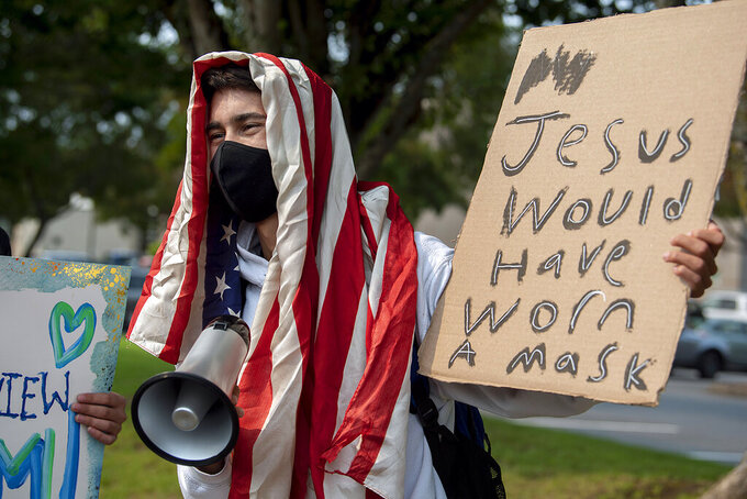 """Skyview High School senior Dylan Walker, 18, shows his support for masks in school during a demonstration with classmates and other protesters in Vancouver, Wash., on Tuesday, Sept. 7, 2021. A Clark County Superior Court judge granted an injunction Tuesday prohibiting protests, rallies or other demonstrations that """"disrupt educational services"""" within one mile of Vancouver schools. The decision followed a lockdown at three schools Friday after some anti-mask protesters tried to enter Skyview High School.(Amanda Cowan/The Columbian via AP)"""