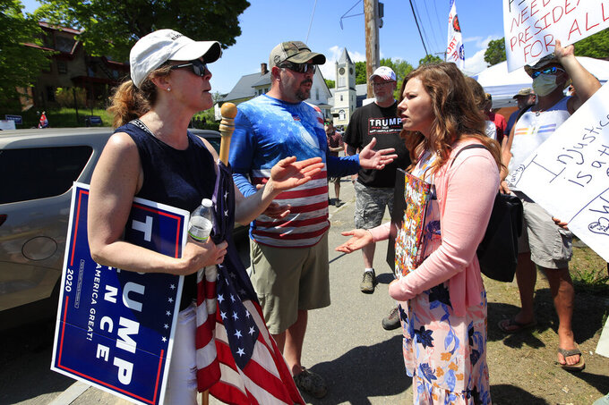 Supporters of President Donald Trump, left and center, argue with a protester prior to the arrival of the president, Friday, June 5, 2020, in Guilford, Maine. Trump is scheduled to visit Puritan Medical Products Co., one of the top two makers of testing swabs in the world. (AP Photo/Robert F. Bukaty)