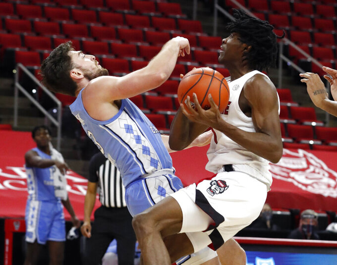 North Carolina State's Dereon Seabron (1) is called for the charging foul as North Carolina's Andrew Platek (3) defends during the first half of an NCAA college basketball game in Raleigh, N.C., Tuesday, Dec. 22, 2020 (Ethan Hyman/The News & Observer via AP)