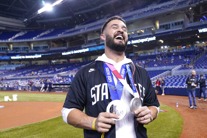 Eddy Alzarez holds his two Olympic silver medals as he meets with the media before a baseball game between the Miami Marlins and the Chicago Cubs, Friday, Aug. 13, 2021, in Miami. Alzvarez won a silver medal in the 5,000-meter speedskating relay in the Winter Olympics in 2014, and a silver medal with Team USA baseball in the Tokyo 2020 Summer Olympics. (AP Photo/Lynne Sladky)