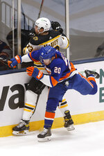 Boston Bruins' Charlie McAvoy (73) and New York Islanders' Kieffer Bellows (20) collide during the second period of an NHL hockey game Monday, Jan. 18, 2021, in Uniondale, N.Y. (AP Photo/Jason DeCrow)