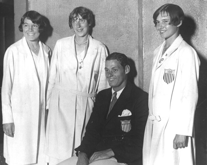 FILE - In this Aug. 22, 1928, file photo, members of the U.S. Olympic team, from left, Katharine Maguire of St. Louis; Dolores Boeck of St. Louis; Johnny Weissmuller, champion swimmer from Chicago; Elizabeth Robinson, 17-year-old sprint champion from Chicago, appear happy to be home as they arrive at the McAlpin Hotel for a reception in New York. (AP Photo/File)