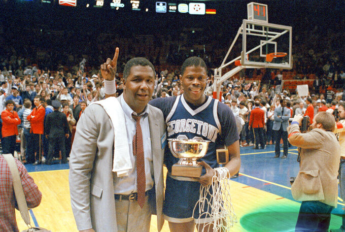 "CORRECTS THAT THE GAME WAS AGAINST ST. JOHNS FOR THE BIG EAST CHAMPIONSHIP, NOT AGAINST HOUSTON FOR THE NCAA CHAMPIONSHIP - FILE - In this March 9, 1985, file photo, Georgetown NCAA college basketball head coach John Thompson poses with player Patrick Ewing after Georgetown defeated St. John's in the Big East Championship in New York.  John Thompson, the imposing Hall of Famer who turned Georgetown into a ""Hoya Paranoia"" powerhouse and became the first Black coach to lead a team to the NCAA men's basketball championship, has died. He was 78 His death was announced in a family statement Monday., Aug. 31, 2020. No details were disclosed.(AP Photo/File)"