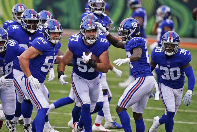 New York Giants defensive end Niko Lalos (57) celebrates an interception with teammates during the second half of an NFL football game against the Cincinnati Bengals, Sunday, Nov. 29, 2020, in Cincinnati. (AP Photo/Bryan Woolston)