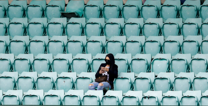 A spectator waits for play to start on day two of the third cricket test between India and Australia at the Sydney Cricket Ground, Sydney, Australia, Friday, Jan. 8, 2021. (AP Photo/Rick Rycroft)