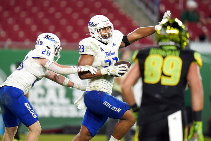 Tulsa linebacker Zaven Collins (23) celebrates with safety Jett Hendrix (28) after Collins intercepted a pass against South Florida and returned it for a score during the second half of an NCAA college football game Friday, Oct. 23, 2020, in Tampa, Fla. (AP Photo/Chris O'Meara)