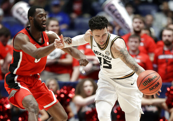 Georgia guard William Jackson II, left, fouls Missouri guard Jordan Geist (15) in the second half of an NCAA college basketball game at the Southeastern Conference tournament, Wednesday, March 13, 2019, in Nashville, Tenn. Missouri won 71-61. (AP Photo/Mark Humphrey)