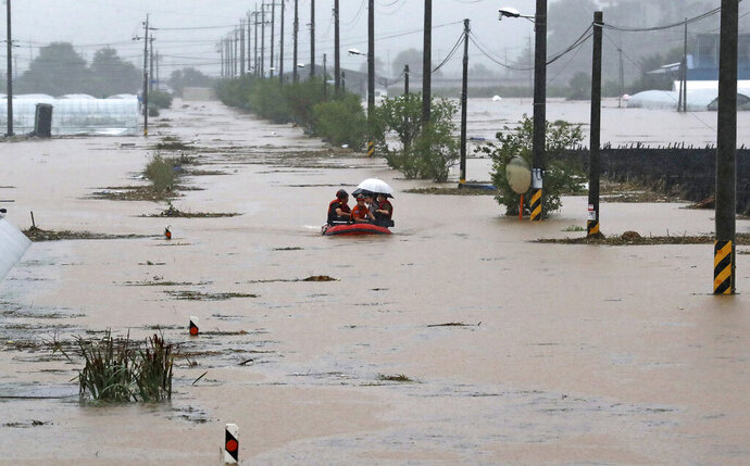 Rescue workers evacuate residents on a rubber boat to a safer place in Cheonan, South Korea, Monday, Aug. 3, 2020. Korean Meteorological Administration issued a warning of heavy rain for Seoul and central area. (Kim Jun-beom/Yonhap via AP)