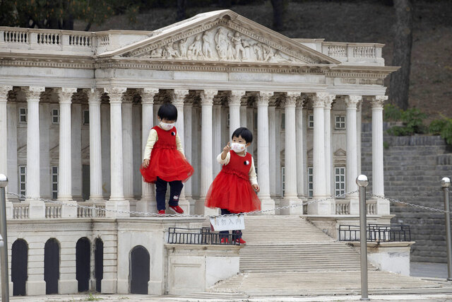 Children wearing face masks stand on the steps of a scaled replica of the United States Capitol Building at the World Park in Beijing on Thursday, May 7, 2020. World tourism has been hard hit by the outbreak of the COVID-19 coronavirus as countries close borders and restricted international flights. (AP Photo/Ng Han Guan)