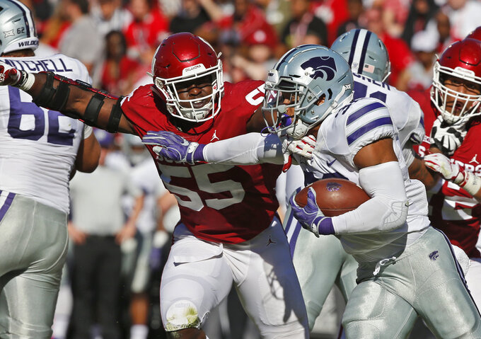 Kansas State running back Justin Silmon,front right, carries around Oklahoma defensive lineman Kenneth Mann (55) in the first half of an NCAA college football game in Norman, Okla., Saturday, Oct. 27, 2018. (AP Photo/Sue Ogrocki)
