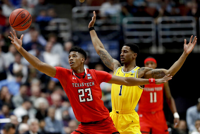 Texas Tech guard Jarrett Culver reaches for a pass as Michigan guard Charles Matthews defends during the first half an NCAA men's college basketball tournament West Region semifinal Thursday, March 28, 2019, in Anaheim, Calif. (AP Photo/Marcio Jose Sanchez)