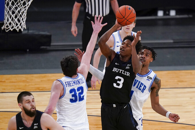 Butler's Chuck Harris, center, drives past Xavier's Paul Scruggs, right, to shoots over Zach Freemantle, second from left, during the first half of an NCAA college basketball game in the Big East conference tournament Wednesday, March 10, 2021, in New York. (AP Photo/Frank Franklin II)