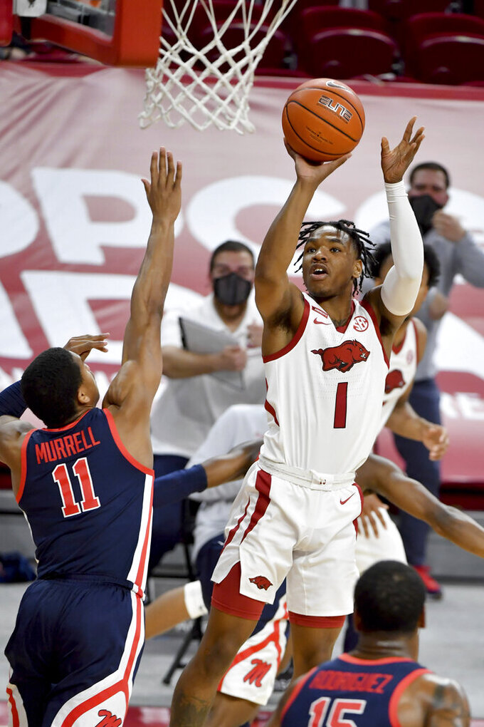Arkansas guard JD Notae (1) shoots over Mississippi defender Matthew Murrell (11) during the first half of an NCAA college basketball game Wednesday, Jan. 27, 2021, in Fayetteville, Ark. (AP Photo/Michael Woods)