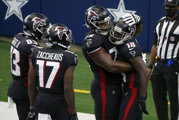 Atlanta Falcons' Russell Gage (83), Olamide Zaccheaus (17) and Matt Gono (73) celebrate with Calvin Ridley, right, after Ridley caught a pass for a touchdown in the first half of an NFL football game against he Dallas Cowboys in Arlington, Texas, Sunday, Sept. 20, 2020. (AP Photo/Michael Ainsworth)