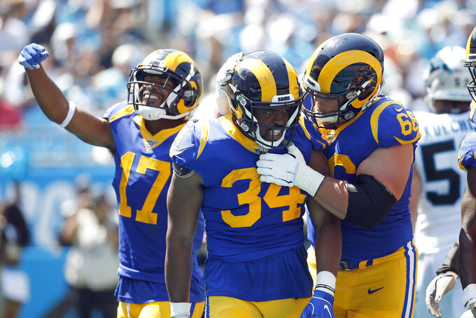Los Angeles Rams running back Malcolm Brown (34) is congratulated by center Austin Blythe (66) and wide receiver Robert Woods (17) following Brown's touchdown against the arolina Panthers during the first half of an NFL football game in Charlotte, N.C., Sunday, Sept. 8, 2019. (AP Photo/Brian Blanco)