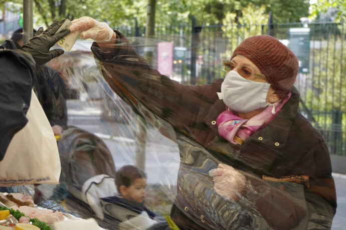 A client gives a banknote to pay a fishmonger wears a face shield as she works at a Paris open air food market, Tuesday, May 12, 2020. Outdoor food markets reopened in Paris on Tuesday as France is cautiously easing the two-month lockdown across the country. Specific measures, such as more widely spaced stalls, have been implemented to enforce physical distancing. (AP Photo/Nicolas Garriga)