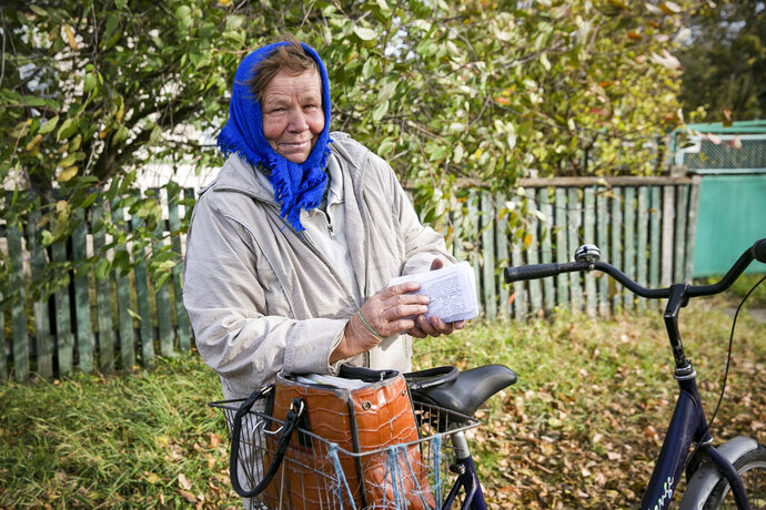 In this Oct. 12, 2019, photo, Tetiana Petrovych, a postmistress, speaks to The Associated Press as she delivers the mail on her bicycle, in the village of Nebelytsia, Ukraine. Most of Ukraine's rich farmland is carved up into small plots owned by about 7 million people, like Petrovych. They are banned from selling it, although the country's new president wants to open the land market. (AP Photo/Andrew Mosienko)