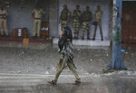 A woman carries her child as she walks past Indian security personnel as it rains during curfew like restrictions in Jammu, India, Monday, Aug. 5, 2019. An indefinite security lockdown was in place in the Indian-controlled portion of divided Kashmir on Monday, stranding millions in their homes as authorities also suspended some internet services and deployed thousands of fresh troops around the increasingly tense region. (AP Photo/Channi Anand)