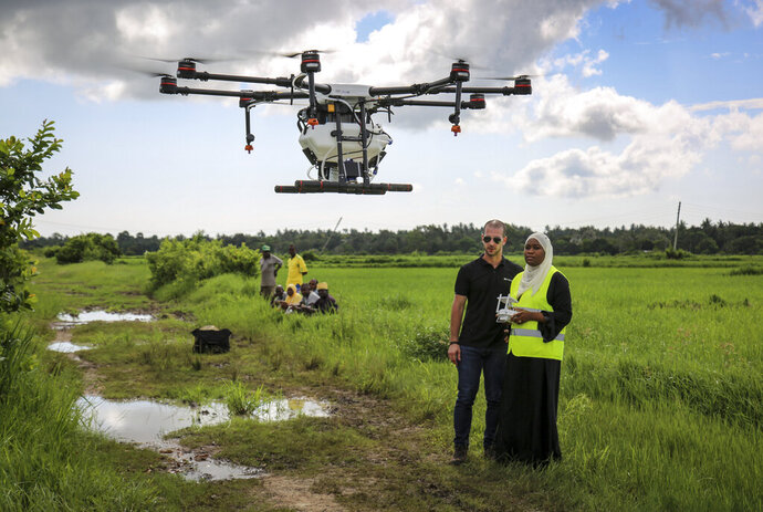 In this photo taken Thursday, Oct. 31, 2019, Eduardo Rodriguez, left, of drone manufacturer DJI, trains Khadija Ali Abdulla, right, from the State University of Zanzibar, how to fly a drone to spray the breeding grounds of malaria-carrying mosquitoes, at Cheju paddy farms in the southern Cheju region of the island of Zanzibar, Tanzania. Drones spraying a silicone-based liquid that spreads across the large expanses of stagnant water where malaria-carrying mosquitoes lay their eggs, are being tested to help fight the disease on the island of Zanzibar, off the coast of Tanzania. (AP Photo/Haroub Hussein)