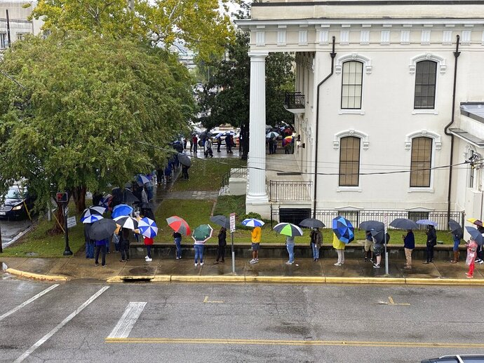 People wait  in the rain to vote in Montgomery, Ala., on Saturday, Oct. 24, 2020. Alabama Secretary of State John Merrill said a record number of absentee ballots have already been cast this year in the election. Some counties allowed Saturday voting for the first time. (AP Photo/Kim Chandler)