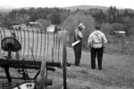 In this April, 15, 1964 photo released by the Vermont State Archives and Records Administration, farmer Romaine Tenney, left, stands with state agent James Wu on his farm in Ascutney, Vt. The Vermont Agency of Transportation is asking the public for ideas for a permanent memorial to Tenney, who took his life after his farm was seized in 1964 to make way for the construction of Interstate 91. A meeting is scheduled for Oct. 29, 2019, at the Ascutney fire station. (Donald Wiedenmayer/Vermont State Archives and Records Administration via AP)