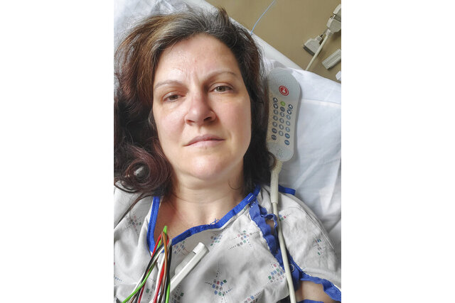 "This May 6, 2020 photo provided by Darlene Gildersleeve, 43, of Hopkinton, N.H. shows her at a Manchester, N.H. hospital. Gildersleeve thought she had recovered from COVID-19. Doctors said she just needed rest. And for several days, no one suspected her worsening symptoms were related — until a May 4 video call, when her physician heard her slurred speech and consulted a specialist. ""You've had two strokes,'' a neurologist told her at the hospital. (Darlene Gildersleeve via AP)"