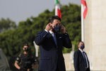 Italian Prime Minister Giuseppe Conte fixes his face mask before addressing Italian soldiers during a visit to an Italian field hospital set up at the Lebanese University in the Hadath district of Beirut, Lebanon, Tuesday, Sept. 8, 2020. Conte said Tuesday his country will support Lebanon's economic and social growth, expressing hopes that a new government is formed quickly — one that would start the reconstruction process in the wake of last month's Beirut explosion and implement badly needed reforms. (AP Photo/Hassan Ammar)