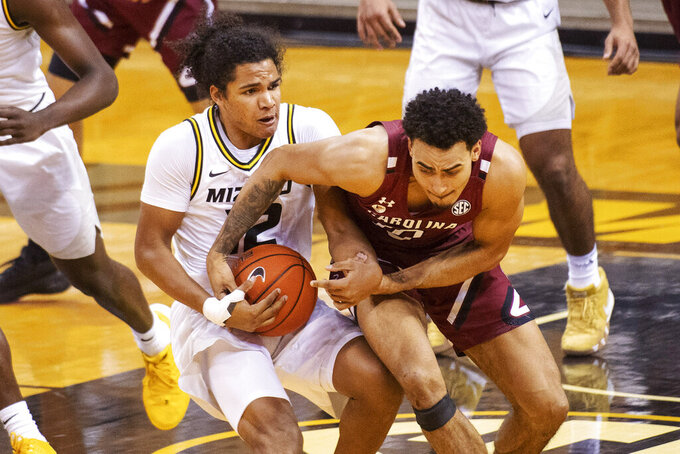 South Carolina's Justin Minaya, right, tries to pull the ball away from Missouri's Dru Smith during the second half of an NCAA college basketball game Tuesday, Jan. 19, 2021, in Columbia, Mo. Missouri won 81-70.(AP Photo/L.G. Patterson)