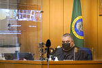 Judge Fa'amomoi Masaniai watches a video feed from a jail courtroom that is also reflected nearby during a hearing for NFL football player Richard Sherman at King County District Court, Thursday, July 15, 2021, in Seattle. Sherman was arrested early Wednesday, police said, after he crashed his car in a construction zone and then tried to break into his in-laws' home in the Seattle suburb of Redmond, Wash. (AP Photo/Elaine Thompson)