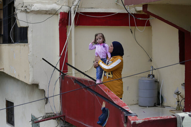 In this Tuesday, May 5, 2020 photo, Faiqqa Homsi holds her daughter Maya, who was diagnosed with cancer, on her apartment balcony in the Mulawiya slum of the northern city of Tripoli, Lebanon. Residents of Lebanon's poorest city, Tripoli, despair as the country faces a terrifying confluence of events. An unprecedented economic crisis, nationwide protests and coronavirus restrictions are posing the biggest threat to stability since the end of the civil war in 1990. Nowhere is the pain more felt than in Tripoli, hometown of Homsi, a mother of five who feels her family is being pushed closer to the edge. (AP Photo/Hassan Ammar)