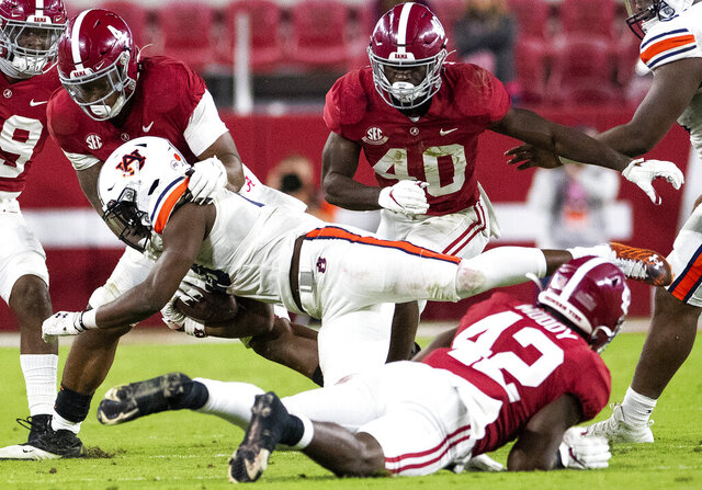Alabama linebackers Christopher Allen (4) and Jaylen Moody (42) stop Auburn running back Mark-Antony Richards (28) during an NCAA college football game Saturday, Nov. 28, 2020, in Tuscaloosa, Ala. (Mickey Welsh/The Montgomery Advertiser via AP)