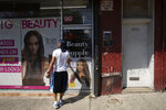 A man enters a store at the sidewalk area where Eric Garner was apprehended by police in the Staten Island borough of New York, Tuesday, July 16, 2019. Federal prosecutors won't bring charges against New York City police officer Daniel Pantaleo in the 2014 chokehold death of Garner. (AP Photo/Mark Lennihan)