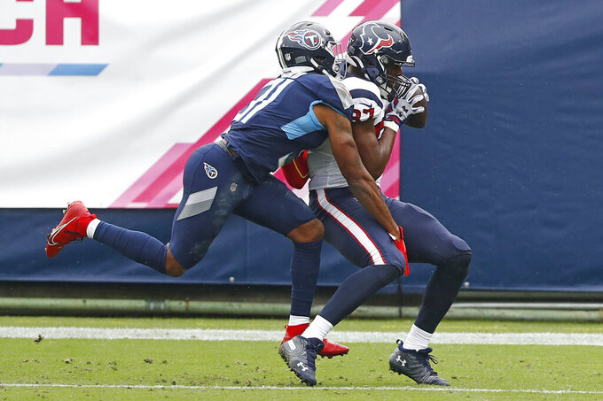Houston Texans tight end Darren Fells, right, catches a touchdown pass as he is defended by Tennessee Titans free safety Kevin Byard (31) in the first half of an NFL football game Sunday, Oct. 18, 2020, in Nashville, Tenn. (AP Photo/Wade Payne)