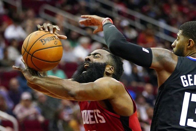FILE - In this March 5, 2020, file photo, Houston Rockets' James Harden, left, is fouled by Los Angeles Clippers' Paul George during the second half of an NBA basketball game in Houston. The photo was part of a series of images by photographer David J. Phillip which won the Thomas V. diLustro best portfolio award for 2020 given out by the Associated Press Sports Editors during their annual winter meeting. (AP Photo/David J. Phillip, File)