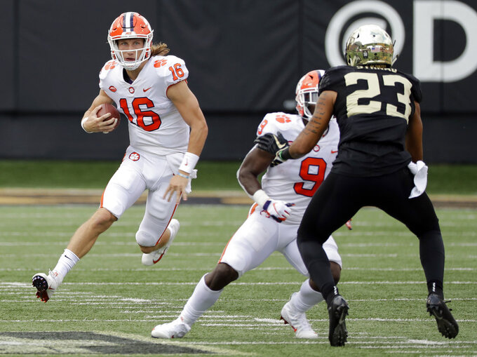 Clemson's Trevor Lawrence (16) scrambles as Wake Forest's Justin Strnad (23) defends during the first half of an NCAA college football game in Charlotte, N.C., Saturday, Oct. 6, 2018. (AP Photo/Chuck Burton)