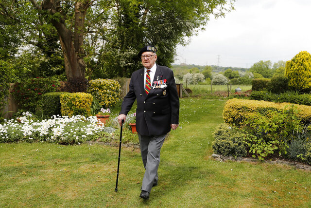 World War II veteran Ken Hay walks in his garden in London, Monday, May 4, 2020. VE-Day was the end of four days of celebration for Ken Hay. It began when the former prisoner of war got his first sight of home in almost a year from a Lancaster bomber he flew back in. (AP Photo/Frank Augstein)