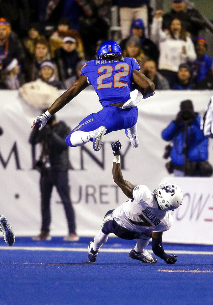 Boise State running back Alexander Mattison (22) hurdles Utah State cornerback DJ Williams (7) during the first half of an NCAA college football game Saturday, Nov. 24, 2018, in Boise, Idaho. (AP Photo/Steve Conner)