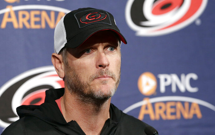 FILE - In this May 9, 2018, file photo, Carolina Hurricanes owner and CEO Tom Dundon takes questions during an NHL hockey news conference in Raleigh, N.C. Dundon is investing $250 million in the Alliance of American Football. Dundon also will serve as chairman of the fledgling eight-team league that began play on Feb. 9. His involvement came together in a matter of days last week, according to Dundon and Alliance co-founder Charlie Ebersol, though Dundon had been monitoring the AAF's development and debut. Ebersol dismissed reports Tuesday, Feb. 19, 2019, that the Alliance was getting a financial bailout from Dundon.(AP Photo/Gerry Broome, File)