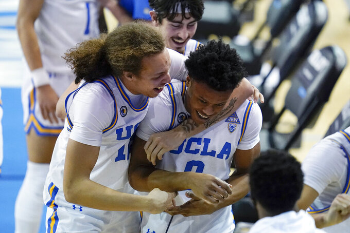 UCLA forward Mac Etienne, left, celebrates with guard Jaylen Clark (0) after Clark made a free throw to give UCLA the lead in the final seconds of an NCAA college basketball game against Arizona State on Saturday, Feb. 20, 2021, in Los Angeles. UCLA won 80-79. (AP Photo/Ashley Landis)
